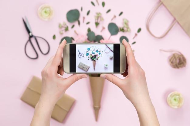 Bovenaanzicht van het nemen van mobiele foto van rozen, eucalyptusbladeren, takken, notitieboekje, schaar
