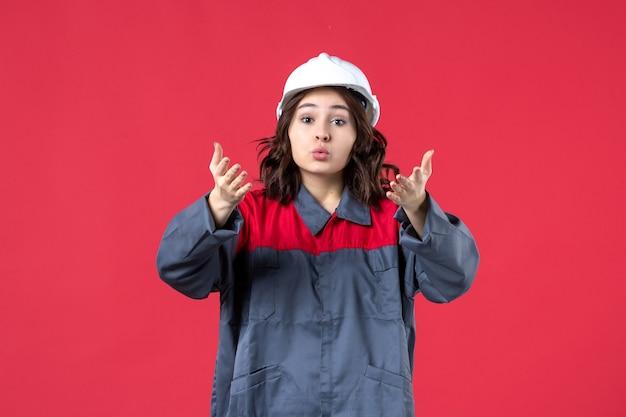 Bovenaanzicht van het ondervragen van vrouwelijke bouwer in uniform met harde hoed op geïsoleerde rode achtergrond