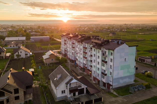 Bovenaanzicht van het ontwikkelen van stadslandschap. flatgebouw en voorstadhuisdaken op roze hemel bij zonsopgangachtergrond.