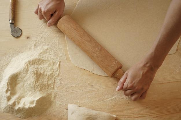 Bovenaanzicht van het proces van zelfgemaakte farfalle pasta. de kok kneedt het deeg op een houten snijplank