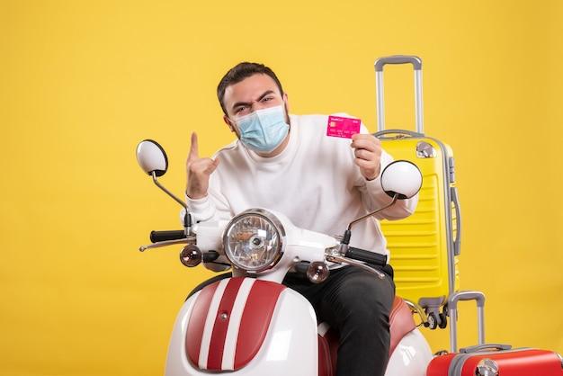 Bovenaanzicht van het reisconcept met een emotionele man met een medisch masker die op een motorfiets zit met een gele koffer erop en een bankkaart vasthoudt