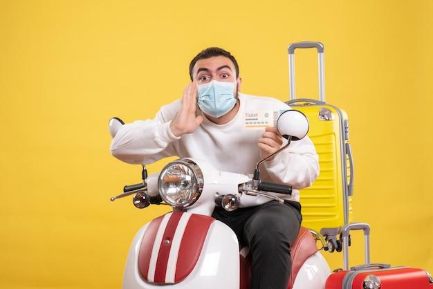 Bovenaanzicht van het reisconcept met een jonge, bezorgde man met een medisch masker die op een motorfiets zit met een gele koffer erop en een kaartje vasthoudt