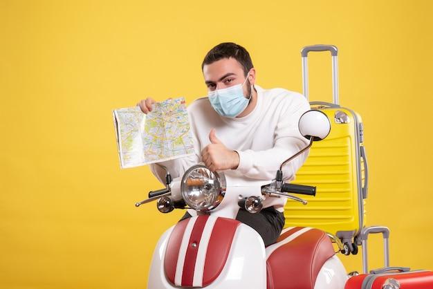 Bovenaanzicht van het reisconcept met een jonge kerel met een medisch masker die in de buurt van een motorfiets staat met een gele koffer erop en een kaart vasthoudt die een goed gebaar maakt