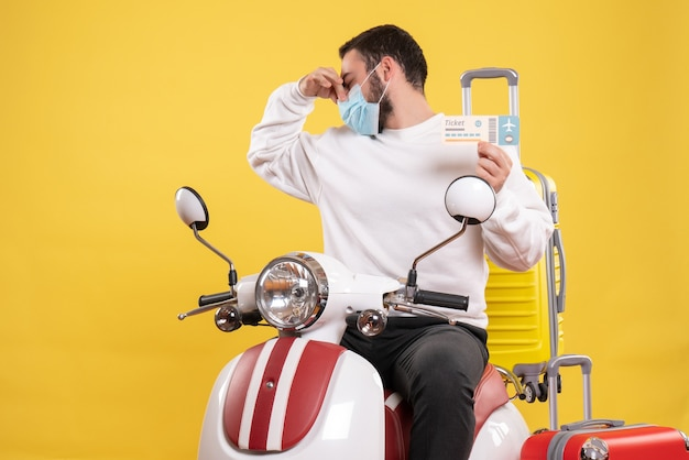 Bovenaanzicht van het reisconcept met een jonge kerel met een medisch masker die op een motorfiets zit met een gele koffer erop en een kaartje vasthoudt dat een stankgebaar maakt