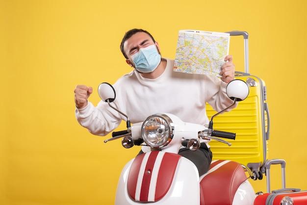 Bovenaanzicht van het reisconcept met een trotse gelukkige man met een medisch masker dat in de buurt van een motorfiets staat met een gele koffer erop en een kaart vasthoudt