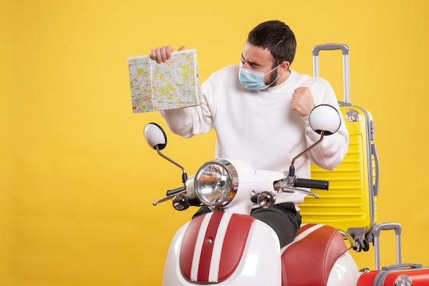 Bovenaanzicht van het reisconcept met een trotse man met een medisch masker die in de buurt van een motorfiets staat met een gele koffer erop en een kaart vasthoudt