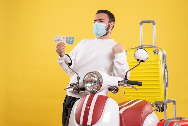 Bovenaanzicht van het reisconcept met een trotse man met een medisch masker die in de buurt van een motorfiets staat met een gele koffer erop en een kaartje vasthoudt