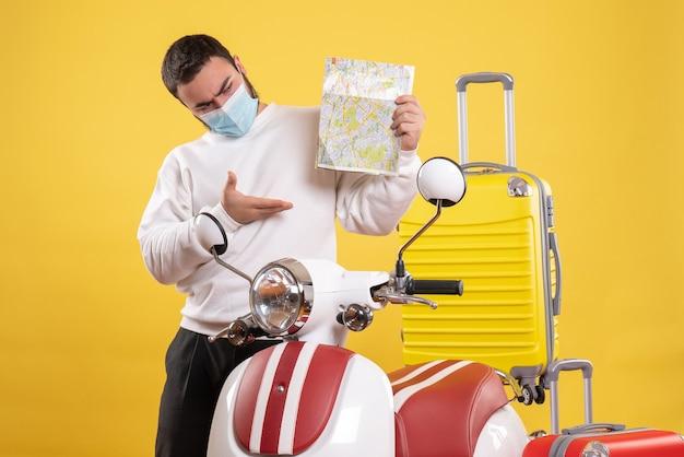 Bovenaanzicht van het reisconcept met een verbaasde man met een medisch masker die in de buurt van een motorfiets staat met een gele koffer erop en een kaart vasthoudt