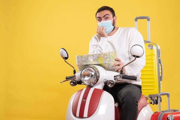 Bovenaanzicht van het reisconcept met een verwarde man met een medisch masker die op een motorfiets zit met een gele koffer erop en een kaart vasthoudt