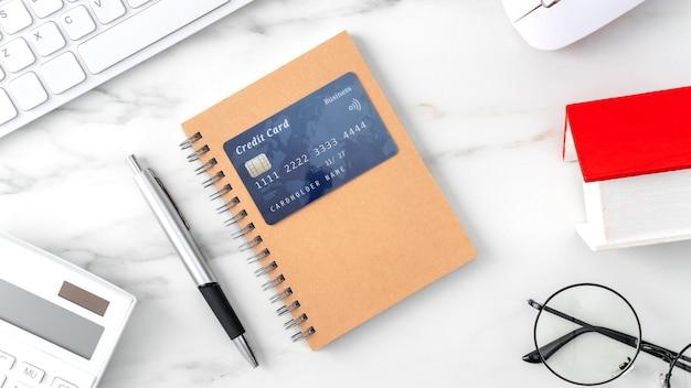 Bovenaanzicht van het schatten en betalen van huisbelasting met rekenmachine en creditcard van internet.