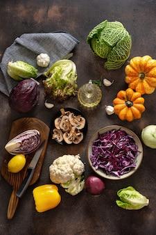 Bovenaanzicht van het snijden van groenten op rustieke tafel