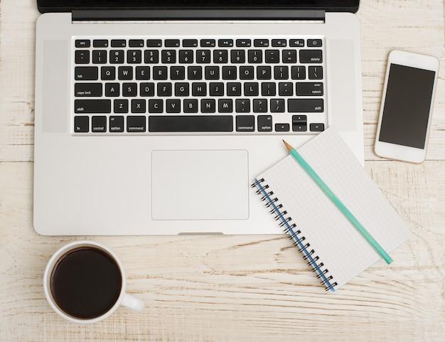 Bovenaanzicht van het toetsenbord van een laptop, slimme telefoon, een notitieboekje met een potlood en een kopje koffie