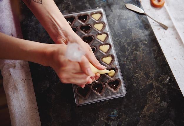 Bovenaanzicht van het uitknijpen van vulling van gezouten karamelcrème uit snoepzak in snoepvormen voor het bereiden van handgemaakte chocoladepralines