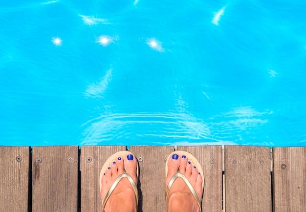 Bovenaanzicht van het zwembad en slippers