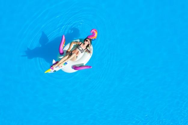 Bovenaanzicht van het zwembad met een meisje in een zwempak op een opblaasbare cirkel. ontspannen en bruinen in de zomer.