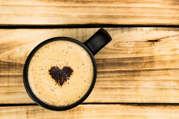 Bovenaanzicht van hete latte of cappuccino koffie in zwarte kop met latte art met hart binnen op houten tafel