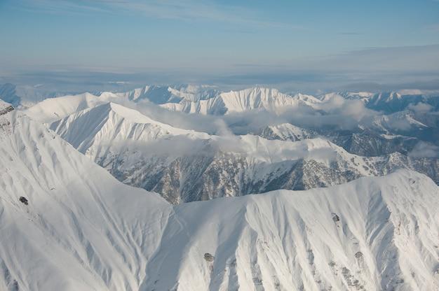 Bovenaanzicht van hoge pure winter bergen bedekt met sneeuw onder de heldere blauwe hemel