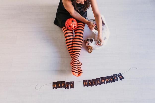Bovenaanzicht van hond liggend op de vloer met een pompoen bovendien en haar eigenaar. vrouw die zwarte en oranje legging draagt. halloween concept. lifestyle binnenshuis