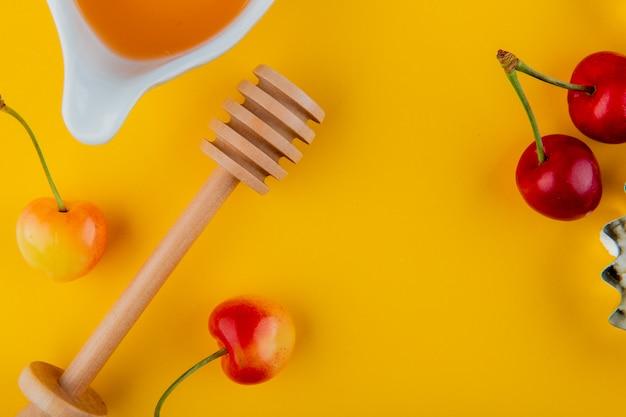 Bovenaanzicht van honing met houten lepel en verse rijpe regenachtigere kersen op geel