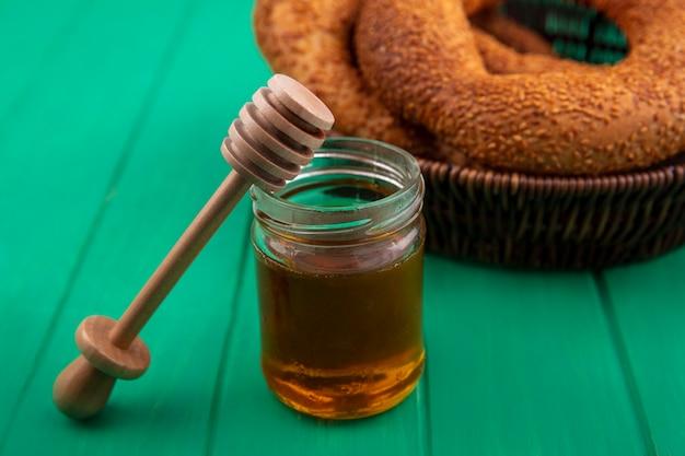 Bovenaanzicht van honing op een glazen pot met houten honinglepel met een emmer broodjes op een groene houten achtergrond