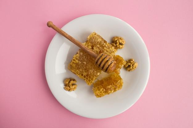 Bovenaanzicht van honingraat en walnoten in de witte plaat op de roze tafel
