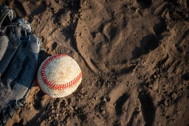 Bovenaanzicht van honkbal en handschoen op vuil
