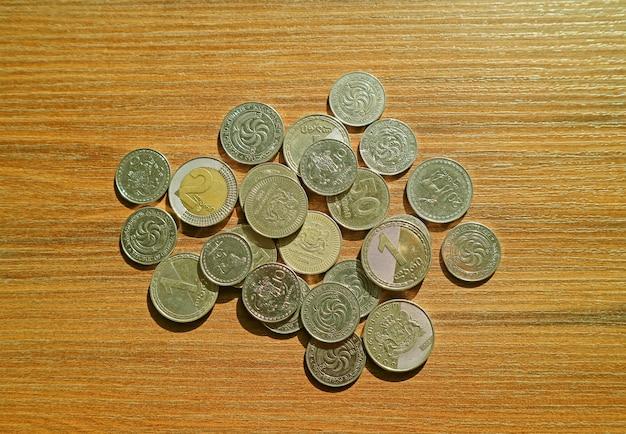 Bovenaanzicht van hoop georgische lari en tetri munten op houten achtergrond