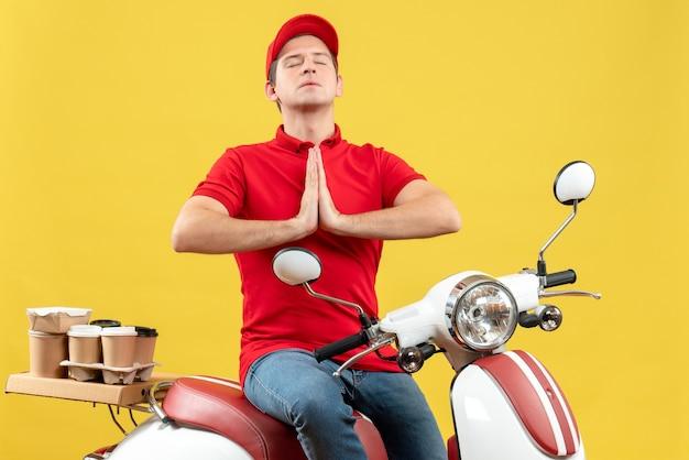 Bovenaanzicht van hoopvolle jonge kerel die rode blouse en hoed draagt die bevelen levert die op gele achtergrond bidden