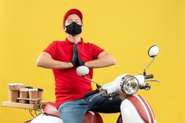 Bovenaanzicht van hoopvolle jonge volwassene dragen rode blouse en hoed handschoenen in medisch masker bestelling zittend op scooter bidden leveren