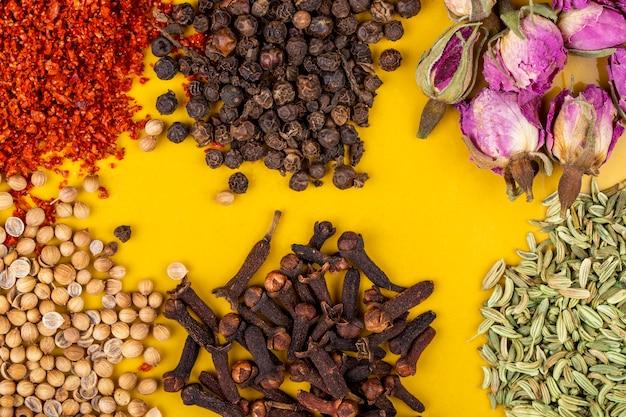 Bovenaanzicht van hopen van specerijen en kruiden op een gele achtergrond