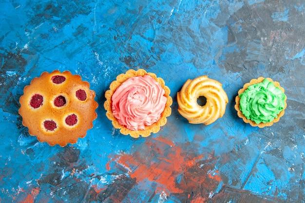 Bovenaanzicht van horizontale rij frambozen cupcakes, kleine taartjes en koekje op blauwe ondergrond