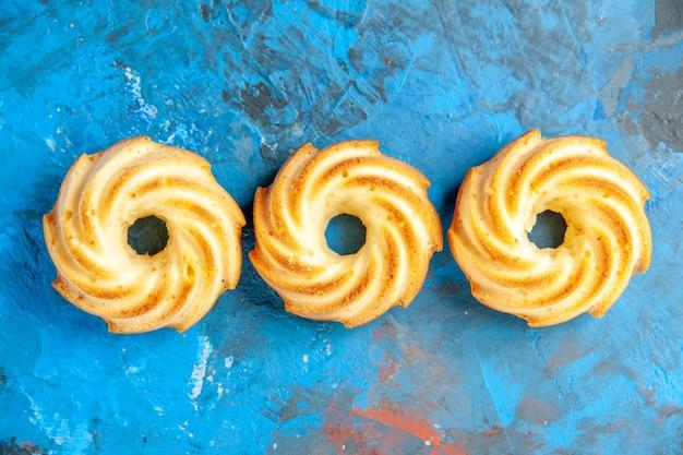 Bovenaanzicht van horizontale rij koekjes op blauwe ondergrond