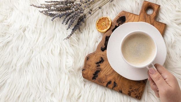 Bovenaanzicht van houder van kopje koffie met lavendel en gedroogde citrus