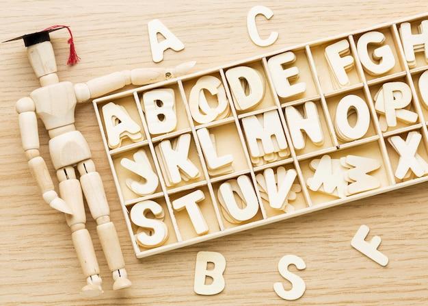 Bovenaanzicht van houten beeldje met academische pet en letters