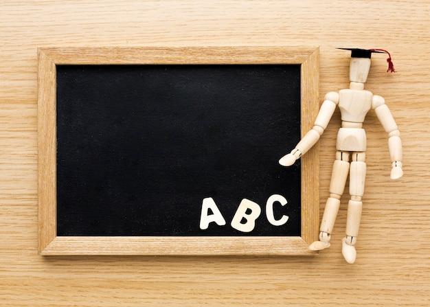 Bovenaanzicht van houten beeldje met academische pet en schoolbord