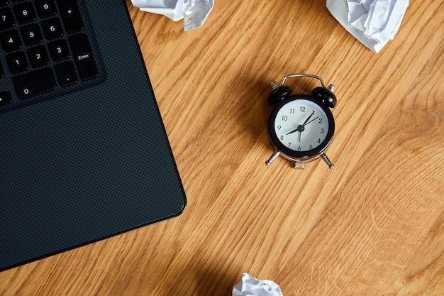 Bovenaanzicht van houten bureau met klok, notebook, verfrommelde papieren ballen, change your mindset, plan b, tijd om nieuwe doelen te stellen, plannen, time management concept, plat leggen.