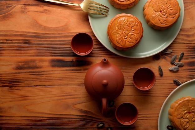 Bovenaanzicht van houten bureau met theeservies, maancakes en kopie ruimte instelling in maanfestival