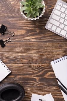 Bovenaanzicht van houten bureau met vetplant en notebooks