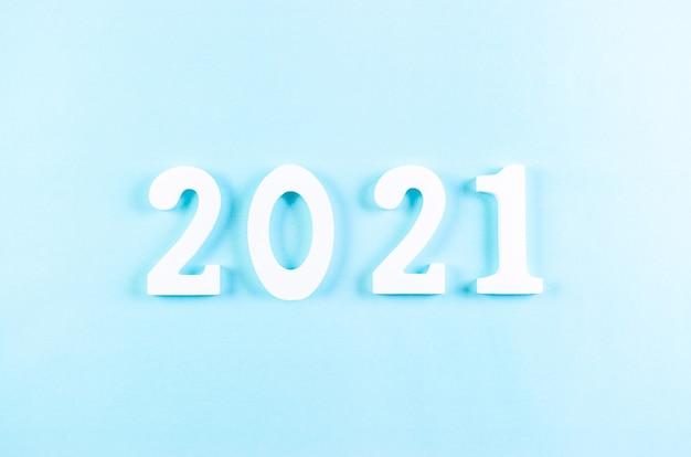 Bovenaanzicht van houten cijfers 2021 op pastelblauw