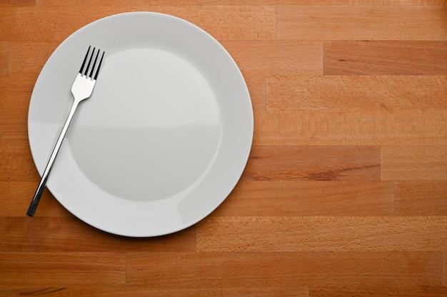 Bovenaanzicht van houten eettafel met mock up keramische plaat vork en kopie ruimte