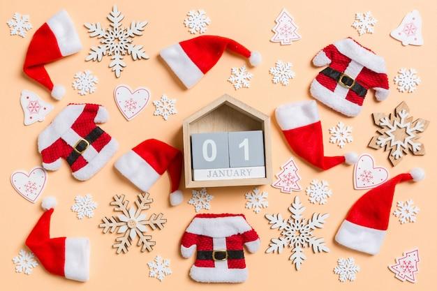 Bovenaanzicht van houten kalender met kerstversiering en kerstmutsen op oranje.
