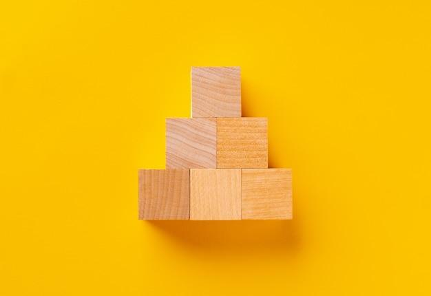 Bovenaanzicht van houten kubussen op gele achtergrond