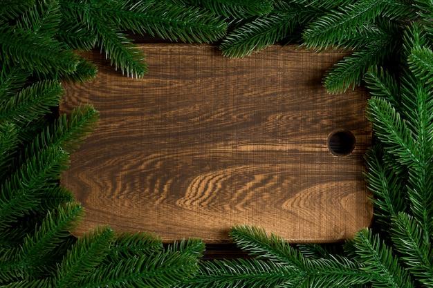 Bovenaanzicht van houten plaat versierd met fir tree takken.