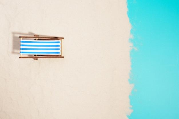 Bovenaanzicht van houten strandstoel op strand.