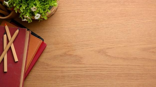 Bovenaanzicht van houten studeertafel met boeken kleurpotloden plant pot en kopie ruimte