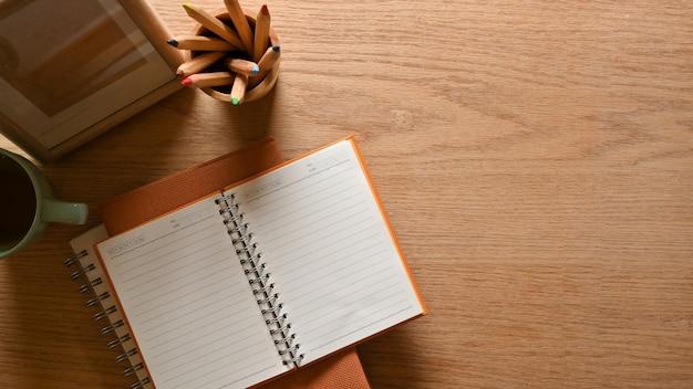 Bovenaanzicht van houten studeertafel met briefpapier beker en kopie ruimte creatieve platte lat werkruimte
