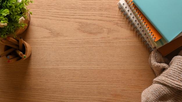Bovenaanzicht van houten tafel met briefpapier trui en kopie ruimte in kantoor aan huis creatieve werkruimte