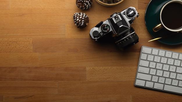 Bovenaanzicht van houten tafel met camera toetsenbord koffiekopje en kopie ruimte Premium Foto