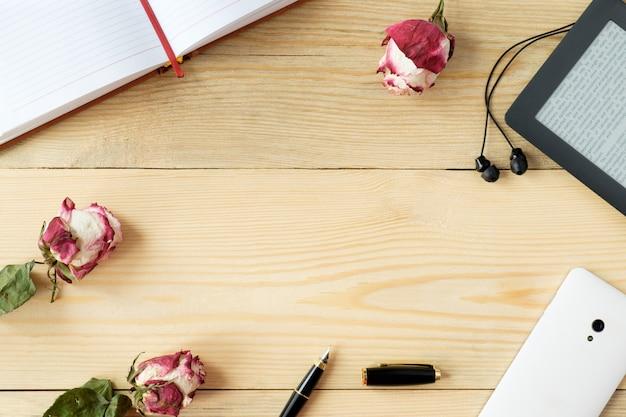 Bovenaanzicht van houten tafel met smartphone, koptelefoon, e-book; stylus pen, dagboek en gedroogde rozen en bladeren
