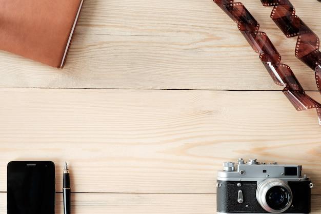 Bovenaanzicht van houten tafel met telefoon; stylus pen, dagboek, vintage camera en film